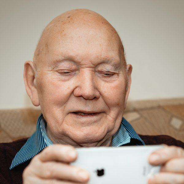 Elderly man watching video on a smartphone.