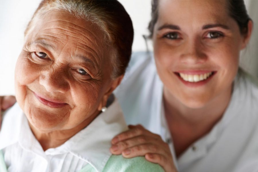 Home care nurse standing with smiling elderly lady.